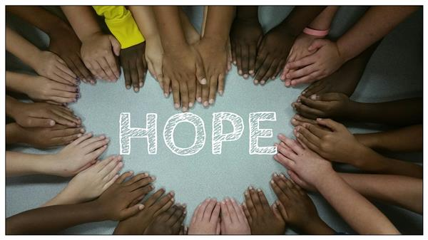 children's hands forming a heart shape around the word hope